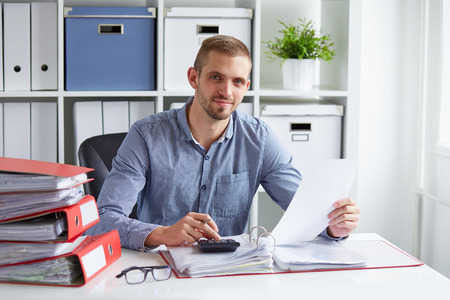 Photo pour Young businessman calculates taxes at desk in office - image libre de droit