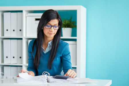 Photo pour Young businesswoman with glasses calculates tax at desk in office - image libre de droit