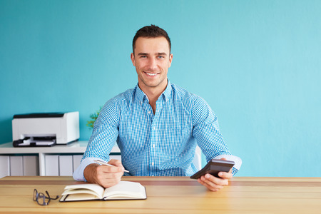 Photo for Happy businessman calculates tax at desk in office - Royalty Free Image