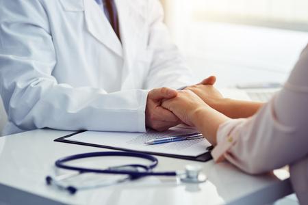 Foto de Friendly male doctor reassuring the patient and holding his hands in the office. - Imagen libre de derechos