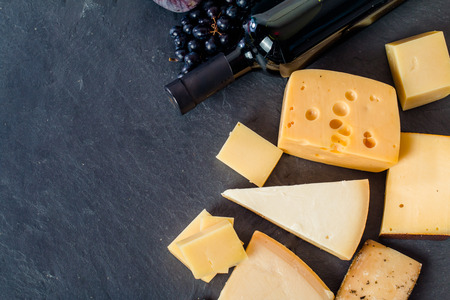 Photo for Different types of cheeses, red wine, grapes and figa on black board, top view - Royalty Free Image