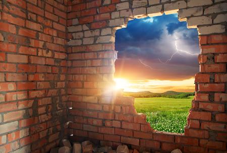 Foto de Broken bricks wal and landscape. Conceptual composition. - Imagen libre de derechos