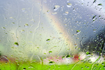 Raindrops on a glass panel with scenery and rainbow in the background