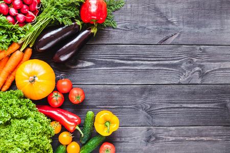 Background of wooden planks black color with fresh vegetables.