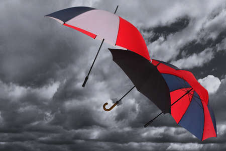 Three umbrellas being blown across a dark stormy cloudy sky
