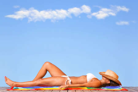 Woman in a white bikini lying on a wooden deck sunbathing with a straw hat over her head.