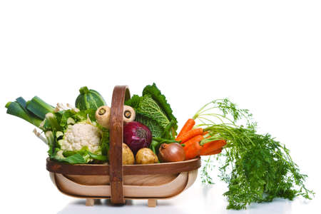 Photo of a wooden trug full of organic vegetables, isolated on a white background.