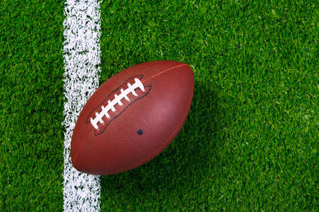 an American football on a grass next to the  touchline, shot from above.