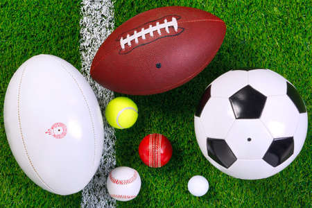 various sports balls on a grass next to the white line, shot from above.