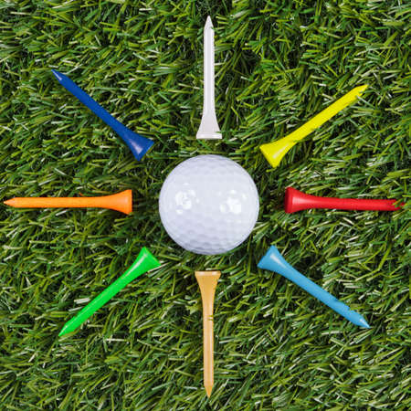 Golf ball with wooden tees arranged around it.