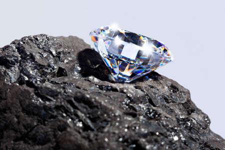 Photo pour Photo of a single cut diamond on a piece of coal against a plain background. - image libre de droit