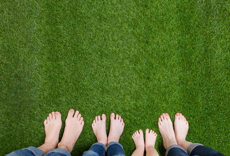 Photo pour Family legs standing on green grass - image libre de droit