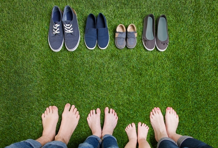 Photo for Family legs in jeans and shoes standing  on grass - Royalty Free Image