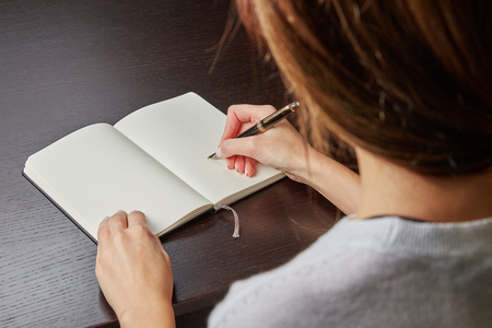 Photo pour Woman writing in a book with a fountain pen - image libre de droit
