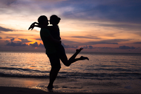 Foto de sunset silhouette of young couple in love hugging at beach - Imagen libre de derechos