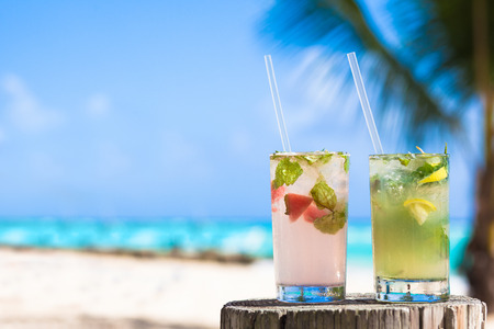 Photo for two glasses of chilled cocktail mohito and sunglasses on table near the beach - Royalty Free Image
