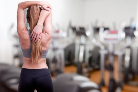 Photo pour Sporty woman stretching her arm, in a gym - image libre de droit