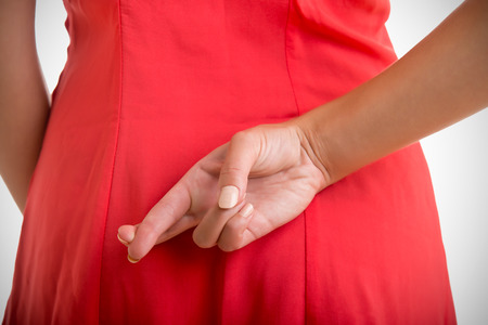 Close up of crossed fingers behind a woman\'s back