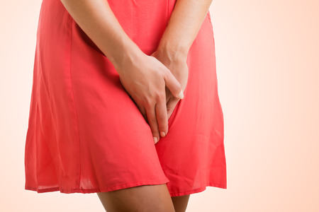 Foto de Close up of a woman with hands holding her crotch, isolated in a pink background - Imagen libre de derechos