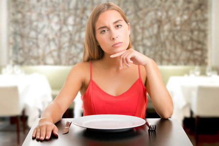 Photo pour Hungry woman on a diet waiting with an empty plate in a restaurant - image libre de droit