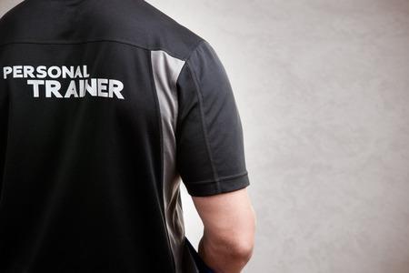 Foto de Personal Trainer, with his back facing the camera, in a grey background - Imagen libre de derechos