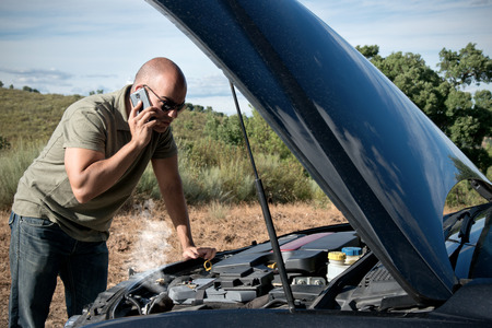 Foto de Close up of a broken down car, engine open and smoking, in a rural area and the driver looking at the engine - Imagen libre de derechos