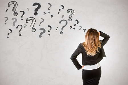 Photo for Backside of a businesswoman with question marks around her, isolated in grey - Royalty Free Image