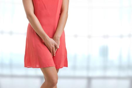 Foto de Close up of a woman with hands holding her crotch, in a blue background - Imagen libre de derechos