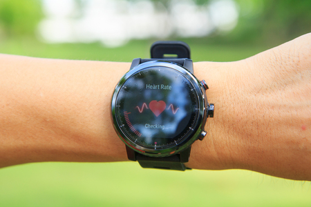 Foto per Checking the heart rate by Amazfit stratos smart watch in the public park - Immagine Royalty Free