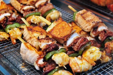 Grilled skewers of seafood consist of salmon, cuttlefish, scampi, and vegetables