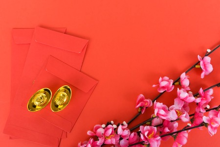 Photo pour Chinese New Year Background Ornaments, Red Envelopes, Plum Flowers and Gold Ingots with Chinese Character Happiness and Prosperity. Red background. - image libre de droit