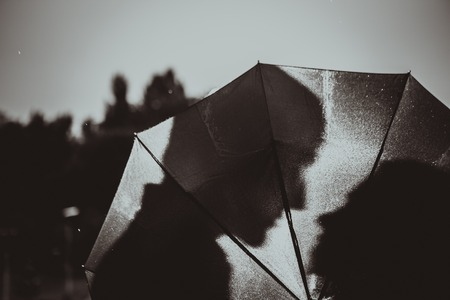Photo for Love in the rain / Silhouette of kissing couple under umbrella - Royalty Free Image