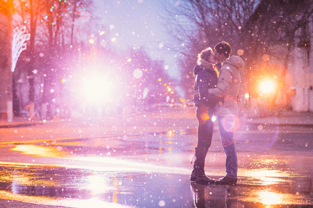 Foto de In love couple kissing in the snow at night city street. Filtered with grain and light flashing - Imagen libre de derechos