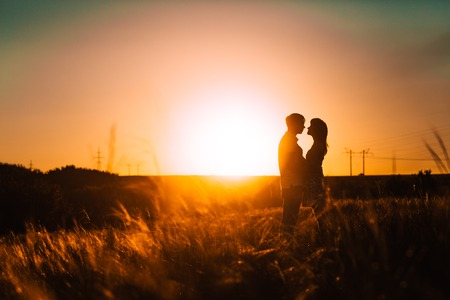 Foto de Romantic silhouette  couple standing and kissing on background summer meadow sunset - Imagen libre de derechos