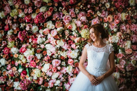 Photo for beautiful bride on the background of a wall of flowers - Royalty Free Image