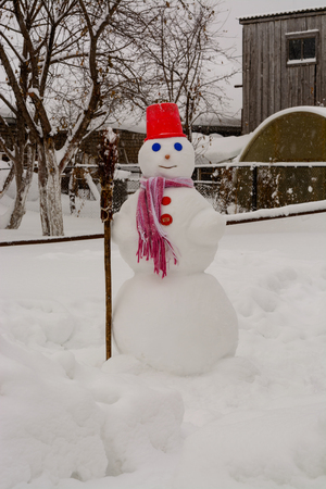 homemade Snowman stands in winter landscape smiling at the camera in the yard
