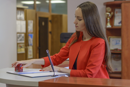 Foto de Young businesswoman or notary, on the Desk in office and stamping document - Imagen libre de derechos