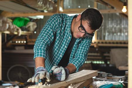 Photo pour carpenter planes wood hand planing machine in the home workshop. - image libre de droit