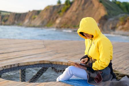 Foto de girl in yellow jacket uses tablet sitting on wooden pier by the sea - Imagen libre de derechos