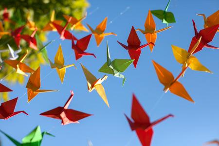 Foto de Colorful origami birds flying. Sky background. - Imagen libre de derechos