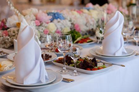 Foto de Served for a banquet table. Wine glasses with napkins, glasses and salads. - Imagen libre de derechos
