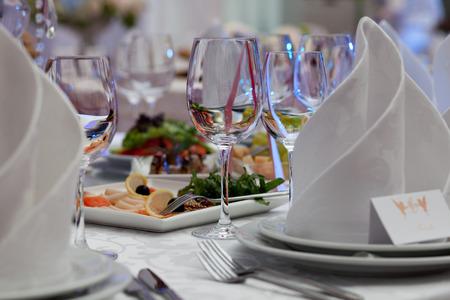 Foto de Wine glasses, napkins and salad on the table for the banquet. - Imagen libre de derechos