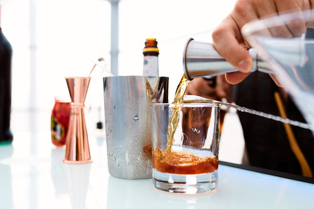 Photo pour bartender pours whiskey into a glass standing on a table in a restaurant - image libre de droit