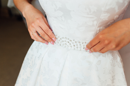 Photo for Bride putting on the wedding dress with a decorated belt - Royalty Free Image