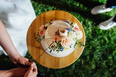 Foto de Happy bride and groom cut the cake. Evening ceremony - Imagen libre de derechos