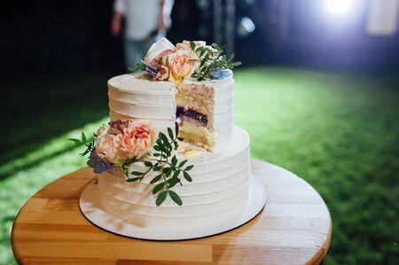 Foto de Happy bride and groom cut the cake. Evening ceremony. Outdoor wedding - Imagen libre de derechos