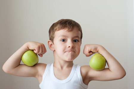 Foto für boy with green apples showing biceps face - Lizenzfreies Bild