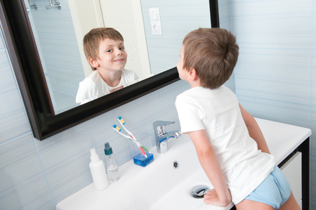 Photo pour happy smiling little kid in blue bathroom looking at himself in the mirror - image libre de droit