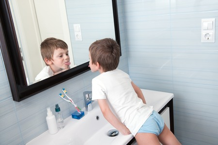 Photo pour funny small boy showing his tongue out in the bathroom mirror - image libre de droit