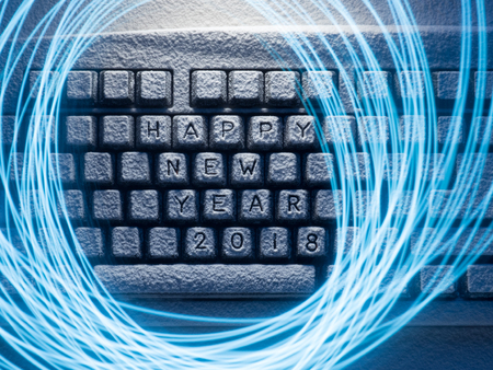 Foto de keyboard covered with snow with inscription happy new year 2018 with painted with light lines - Imagen libre de derechos